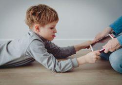 Computersucht? Ein Vater nimmt seinem Jungen den Labtop weg. Es gibt 10 Zeichen, an denen Eltern erkennen können, ob ihr Kind tatsächlich computersüchtig ist