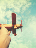 Hand mit Spielzeugflugzeug www.gesundeitsjournalistin.ch