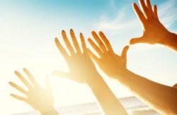 Vitamin D Mangel kann das Risiko für Covid-19 erhöhen. Hände und Sonne. Foto