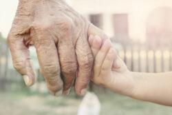 Alte Hand hält Kinderhand Sinnbild Pestizidschäden können sich vererben